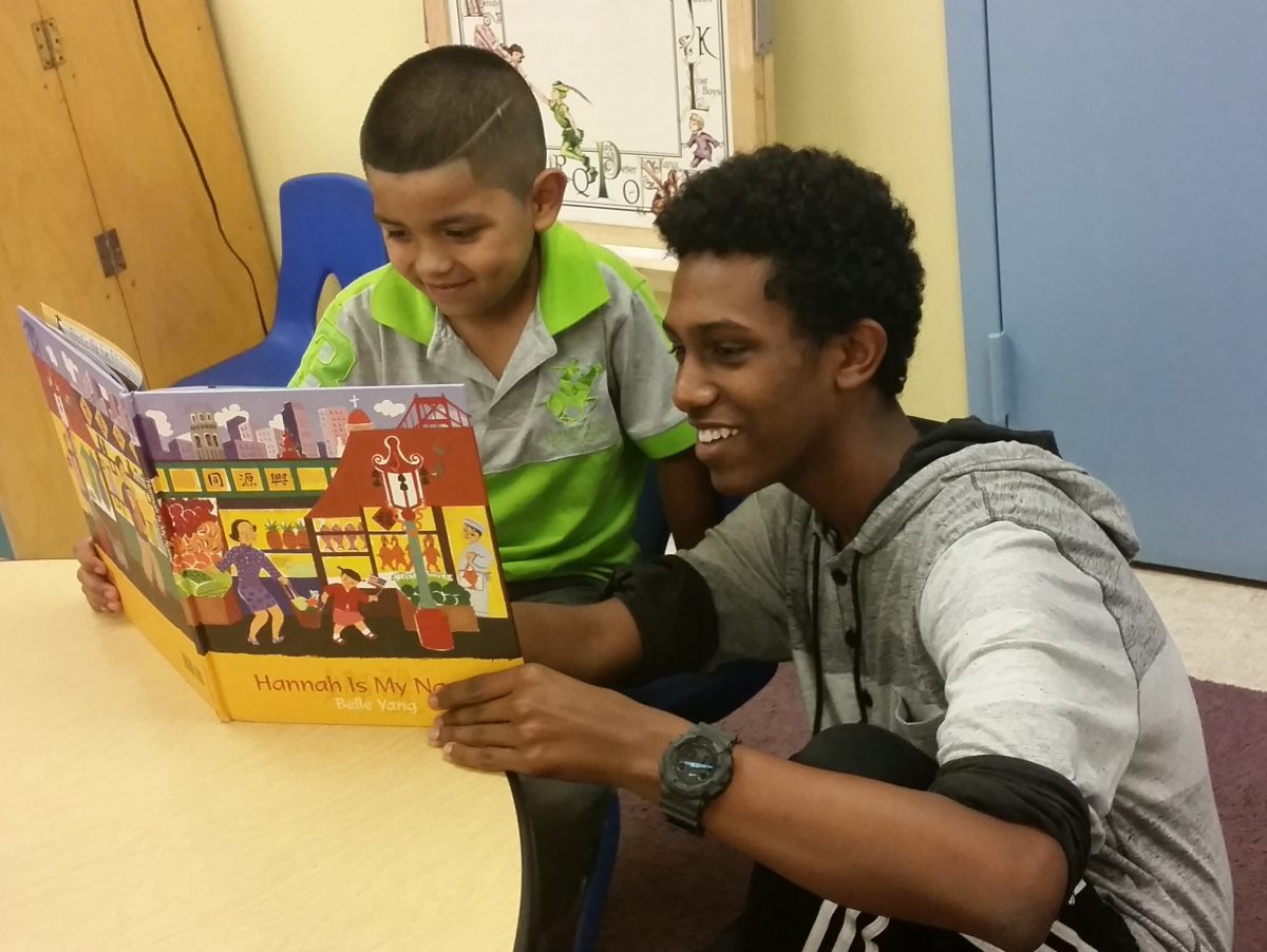 Teen and child read picture book together
