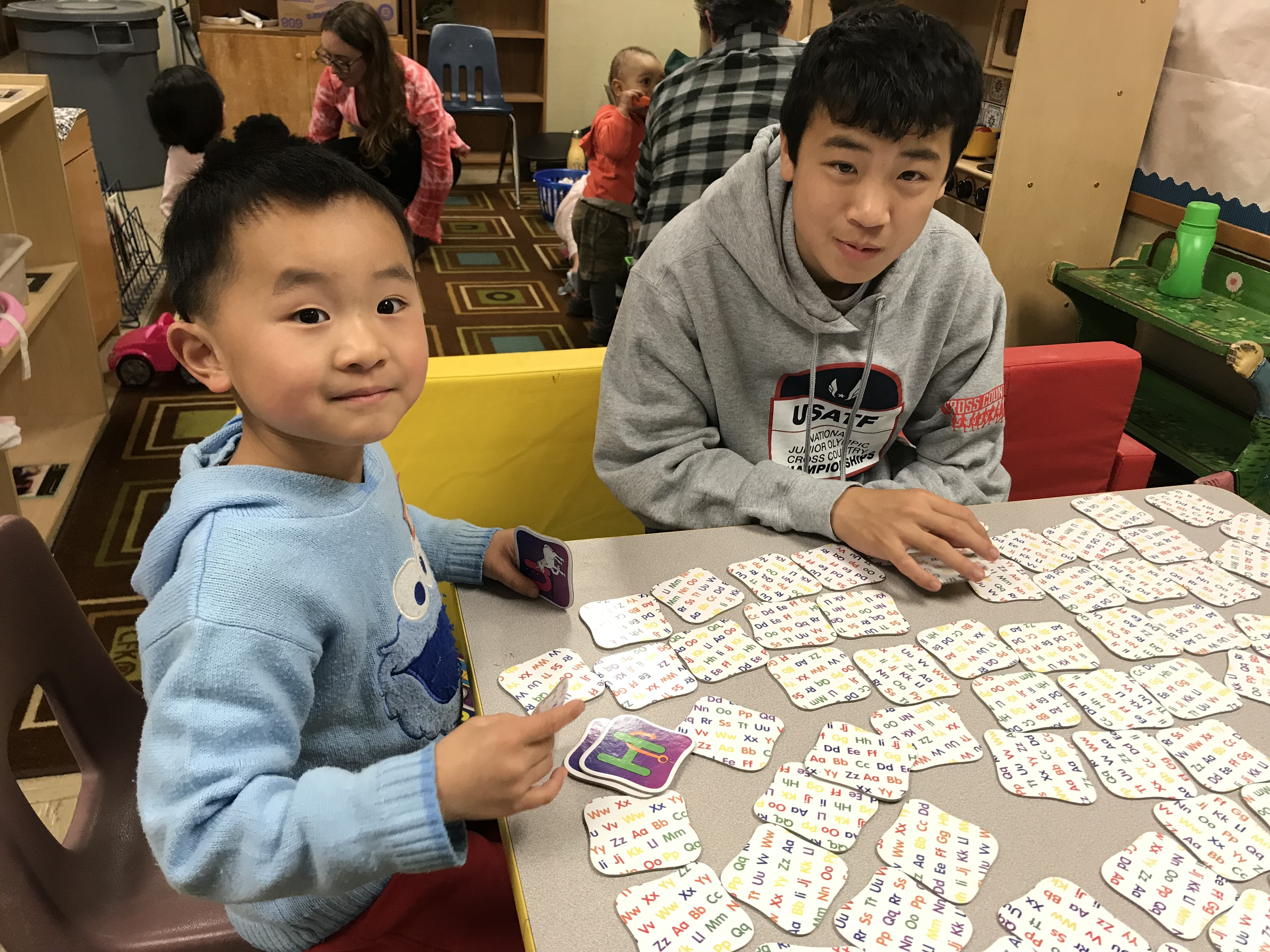 youth and child play cards together