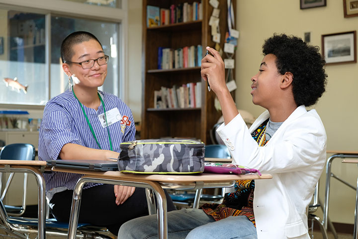 A tutor and student smiling and talking during a classroom tutoring session