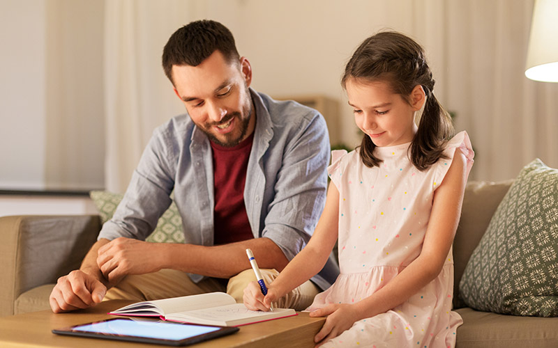 father and daughter doing homework together