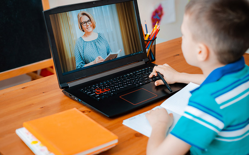 A schoolboy boy studies at home and does schoolwork with an online tutor.