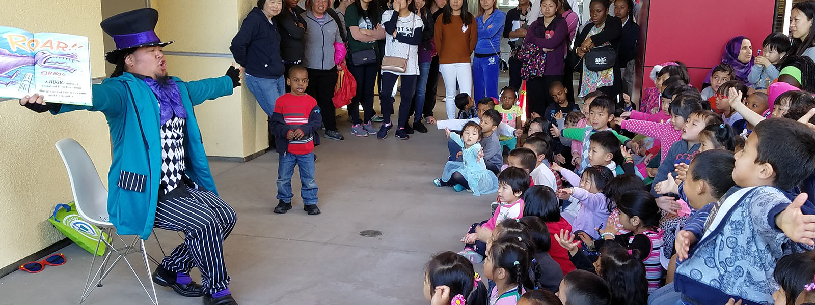 A man in a top hat and costume reads a book to a large group of children and parents